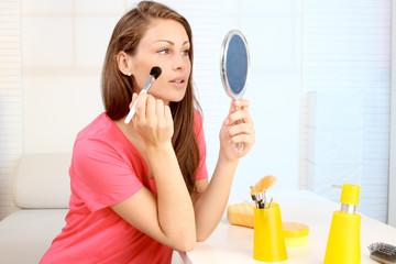Frau pudert ihr Gesicht ab