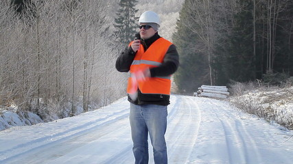 Forest inspector with walkie-talkie in the woods