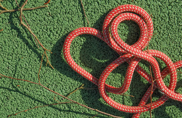 coil of mountaineering rope on green asphalt