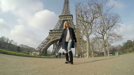 Slow motion of woman jumping near Eiffel tower