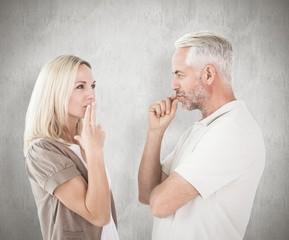 Composite image of couple staying silent with fingers on lips