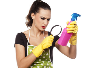 confused young housewife reads the label on the spray bottle