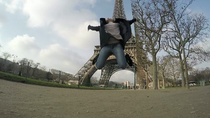 Slow motion of woman jumping near Eiffel tower