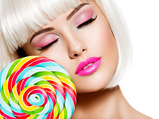 Face of a beautiful  girl with pink make-up and multicolor sweet