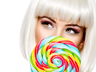 Face of a beautiful   girl with pink eye make-up and sweet candy