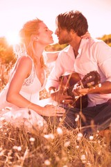 Handsome man serenading his girlfriend with guitar