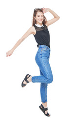 Happy young fashion girl in jeans jumping isolated