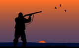 hunter with gun at sunset background