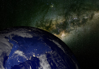 Earth from space at night and the Milky Way.