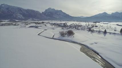 Flug über Flusslandschaft im Winter in den Alpen
