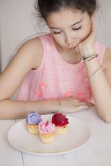 Girl looking at cupcakes