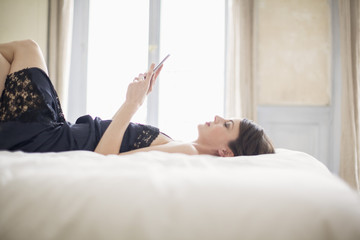 Woman lying on the bed using a mobile phone