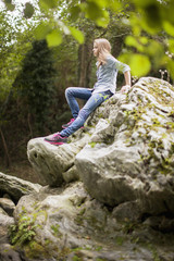 Girl sitting on rock in a park