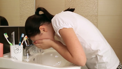 Young girl washing her face in the bathroom