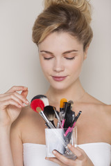 Beautiful woman holding assorted makeup brushes