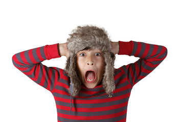 Boy in furry hat puloling funny faces on white background