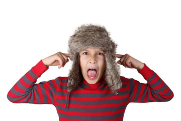 Boy in furry hat pulling funny faces on white background