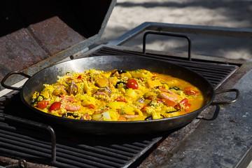Paella wird auf einem Grill zubereitet