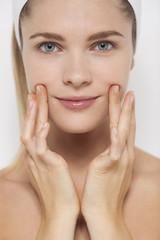 Beautiful woman applying moisturizer on her face