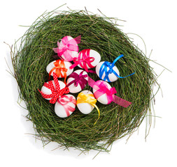 Colorful easter eggs in a nest, top view