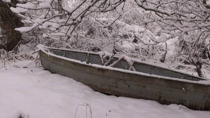 old abandoned wooden boat on winter snow near river