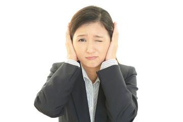 耳を押さえる女性