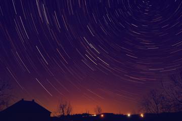 Star trails around Polar star with distant city glow.