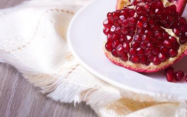 Closeup sliced pomegranate on white plate