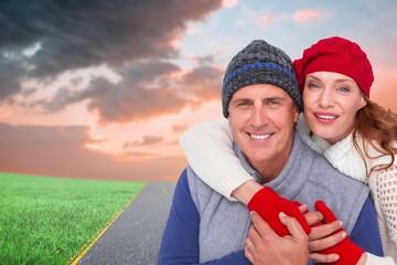 Composite image of happy couple in warm clothing