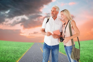 Composite image of happy tourist couple using the guidebook