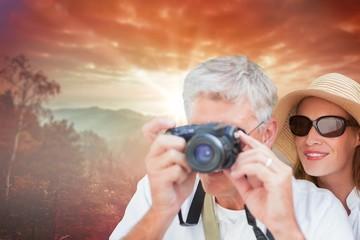 Composite image of vacationing couple taking photo