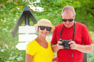 Composite image of happy mature couple wearing sunglasses