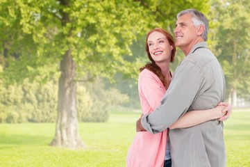 Composite image of casual couple hugging and smiling