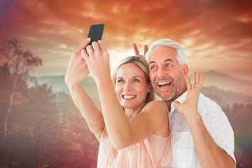 Composite image of happy couple posing for a selfie