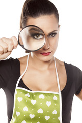 young housewife looking through a magnifying glass