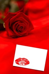 Composite image of red rose resting on red silk