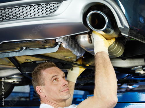 canvas print picture Car mechanic fixing the exhaust system of a car