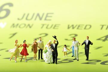 6月のジューンブライドに結婚して大勢の友人に祝福されるカップル