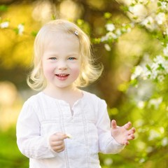 Adorable toddler girl in blooming cherry garden