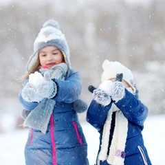 Two little sisters having fun at winter