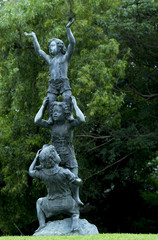 Children in gymnastic action statue in public park.