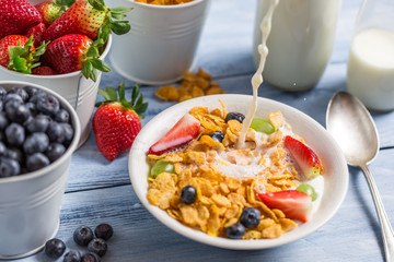 Pouring milk into cornflakes with fruits