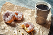 Closeup of hot coffee and donuts on paper