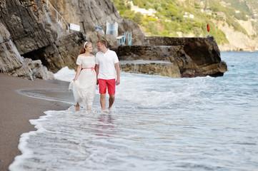 happy couple walking on the beach of Positano in wedding day