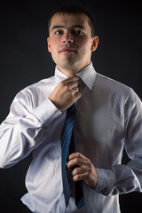 handsome businessman corrects tie isolated on black background