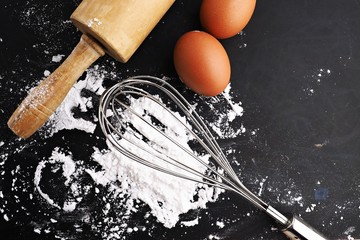 Baking cake ingredients. Bowl, flour, eggs,  on black chalkboard