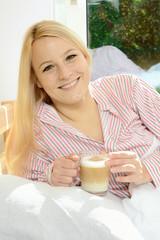 Frau trinkt Milch-Kaffee im Bett