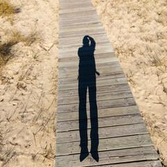 Elongated Shadow Jumping Man on a Wooden Walkway