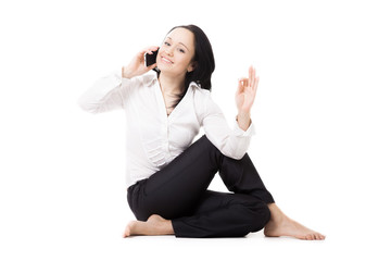 Young business woman in yoga pose making call on white backgroun