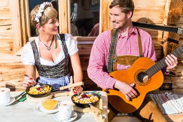 Paar auf Berghütte musiziert isst Kaiserschmarrn